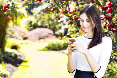 socialising: Beautiful girl with long straight dark hair typing text message on her smart phone in the garden