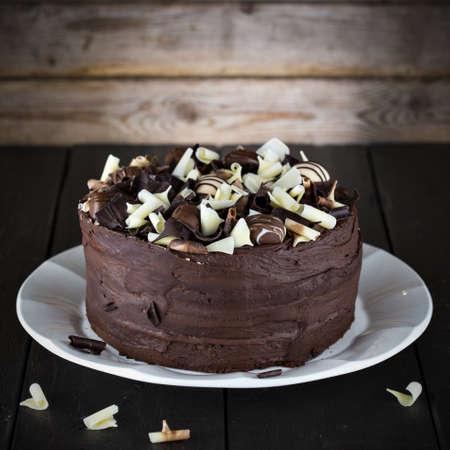 plato: Luxury homemade chocolate cake on dark brown wooden table.