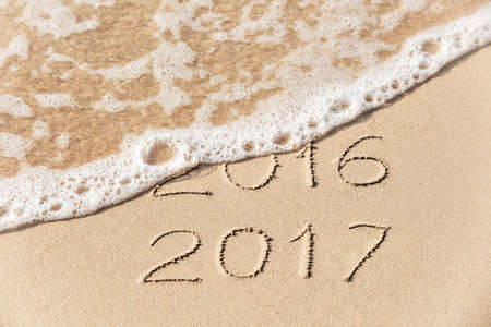2016 2017  inscription written in the wet yellow beach sand being washed with sea water wave. Concept of celebrating the New Year at some exotic place Imagens
