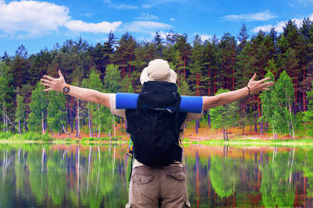 Backpacker with black rucksack spreads hands expressing happiness at picturesque scene of pine forest on calm lake shore. Active summer holiday, camping.