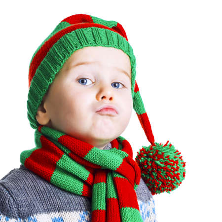 pompon: Small boy with blue eyes in knitted hat, scarf and sweater posing on white background. Christmas kid with facial expression.