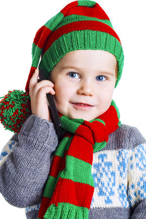 pompon: Little boy in a knitted hat, scarf and sweater makes a phone call to Santa Claus with a Christmas wish. Isolated on white background.