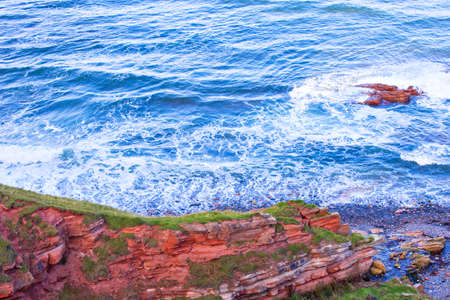 lothian: Red layered cliffs of Scotlands South-East coast at Scottish borders. Stock Photo