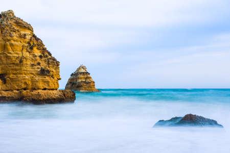 Rocky cliffs of Praia Dona Ana at Lagos, Portugal. Long exposure photography. Stock Photo