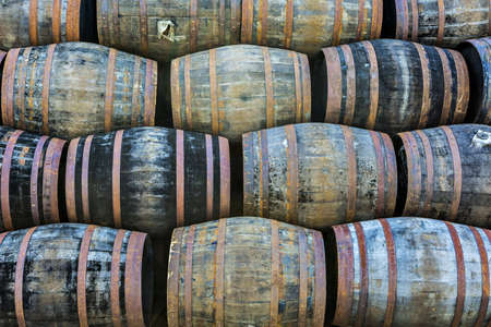 Stacked pile of old wooden barrels and casks at whisky distillery in Scotland. Stock Photo