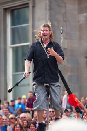 EDINBURGH, SCOTLAND, AUG 5, 2014. Street entertainer balances on unicycle and juggles with burning torch, spanner, and saber on Royal Mile during Edinburgh International Fringe Festival. Editorial