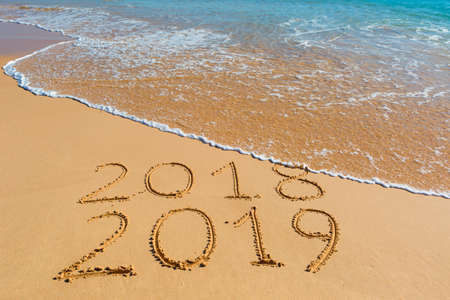 2018 2019 inscription written in the wet yellow beach sand being washed with ocean water wave. Concept of celebrating the New Year at some exotic place. Archivio Fotografico - 111064225