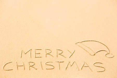 Merry Christmas inscription on wet yellow beach sand. Holiday wish message.