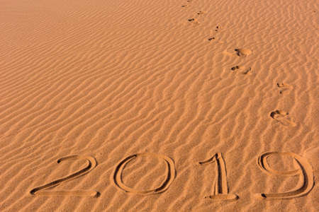 2019 inscription written on golden wavy beach sand dunes with footprints leading away. Concept of celebrating the New Year in some exotic place.