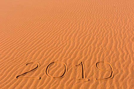 2019 inscription written on golden wavy beach sand dunes. Concept of celebrating the New Year in some exotic place.