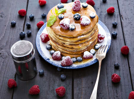 Pile of pancakes with blueberries and raspberries sprinkled with icing sugar and poured on with honey for breakfast on wooden table