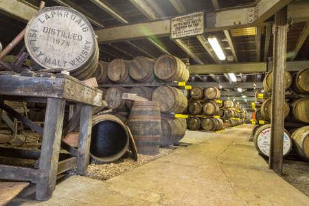 ISLAY, SCOTLAND - SEPT 15 2017 : Old wooden barrels and casks at Lafroaig whisky distillery warehouse established in 1815. Redakční