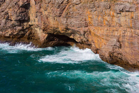 Sea waves hitting rock cliff with a cave at Fortaleza de Sagres, Portugal.