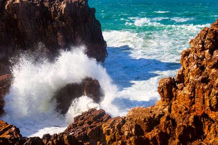 Sea waves hitting rocks cliff at Praia Da Bordeira, Portugal. Фото со стока