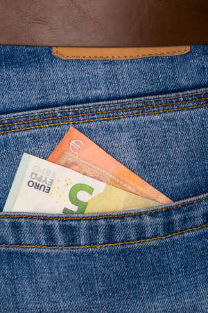 Closeup of five Euro banknote peeking out of blue jeans back pocket. Budget travel or shopping, low earnings, economical crisis concept. Foto de archivo
