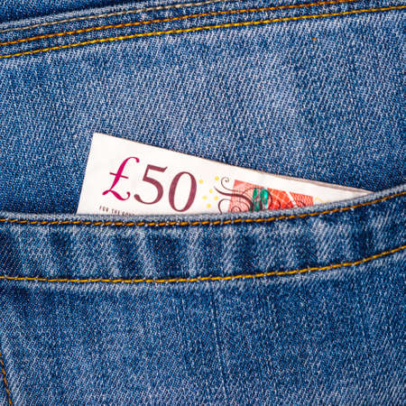 Closeup of fifty pounds sterling banknotes peeking out of blue jeans back pocket. Travel or shopping, good earnings, concept. 免版税图像