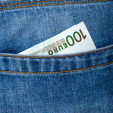 Closeup of one hundred Euro banknote peeking out of blue jeans back pocket. Budget or luxury travel, shopping concept.