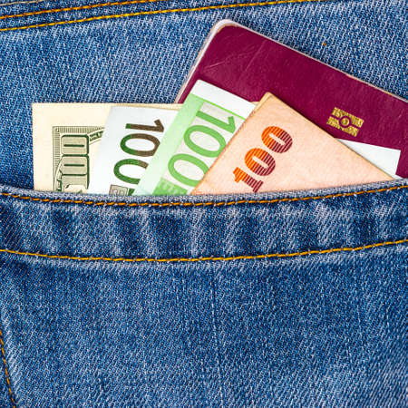 Closeup of various countries hundred banknotes and EU passport peeking out of blue jeans back pocket. Luxury travel or shopping, good earnings, emigration concept.
