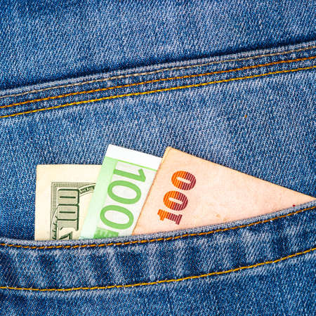 Closeup of various countries hundred banknotes peeking out of blue jeans back pocket. Luxury travel or shopping, good earnings, emigration concept.
