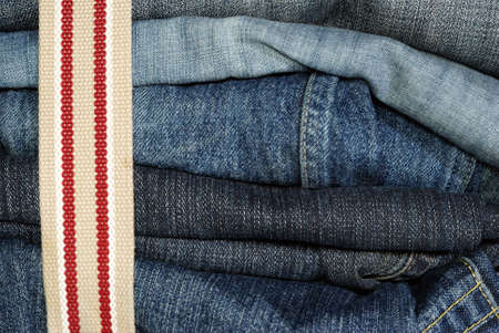 constricted: pile of jeans constricted with belt, higly detailed macro shot Stock Photo