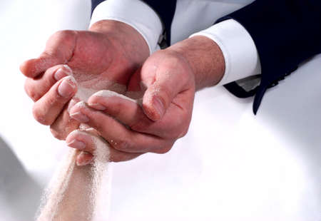 Male business hands trying to hold sand photo