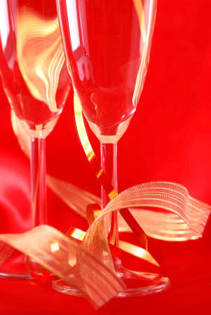 two champagne glasses against a red silk background photo