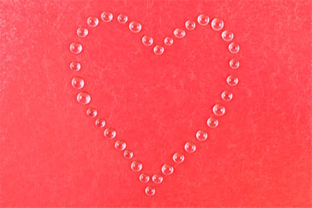 Red heart shape made of water droplets photo