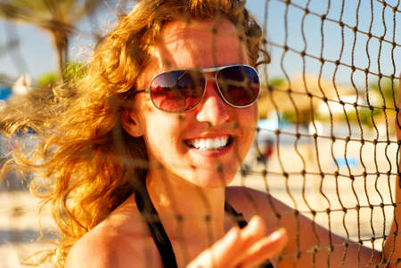 happy woman behind the volleyball net photo