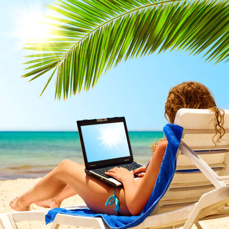 surfing on the beach. Laptop display is cut with clipping path photo