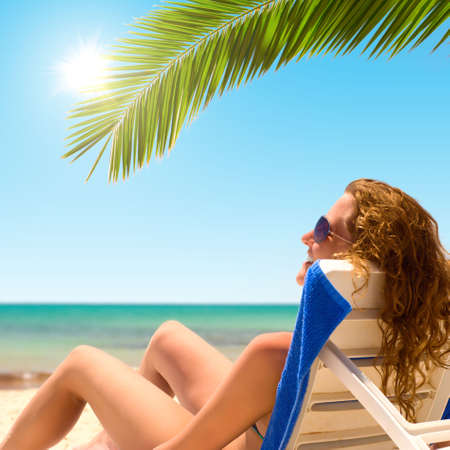 sexy woman sits on chaise longue under a palm tree photo