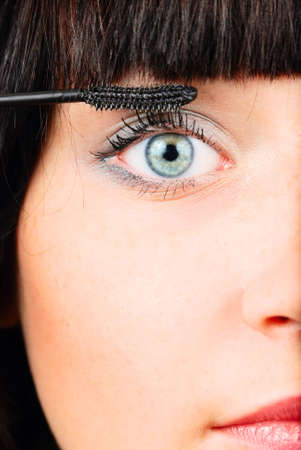 closeup of a woman applying mascara photo