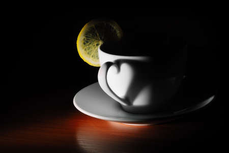 cup with lemon in dark photo