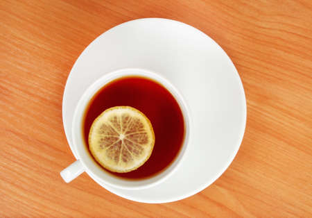 top plan of a tea cup with lemon on wooden table photo