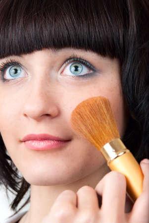 closeup of young woman applying cosmetics photo