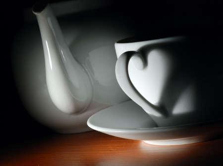 yellow tea pot: tea cup and teapot in dark