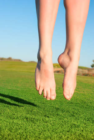 closeup of feet of jumping on green field woman photo