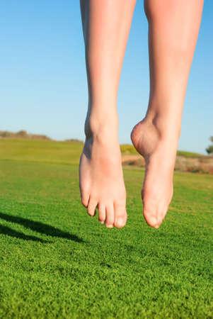 closeup of feet of jumping on green field woman photo