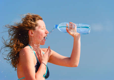 sexy woman is refreshing herself with bottle of water photo