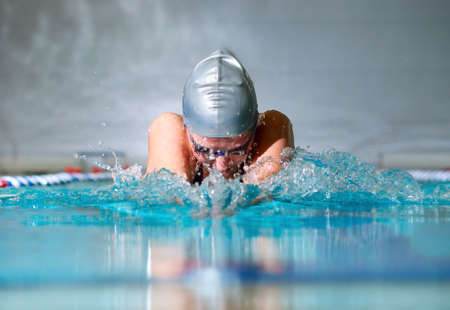 여자는 실내 수영장에서 평영을 사용하여 수영