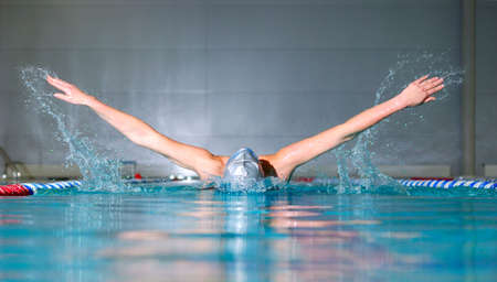 woman swims using the butterfly stroke in indoor pool  photo