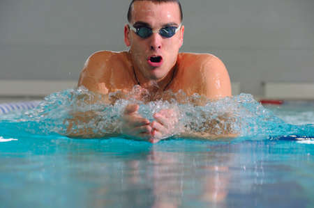 man swims using the breaststroke in indoor pool photo
