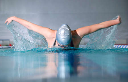 swim suit: woman swims using the butterfly stroke in indoor pool