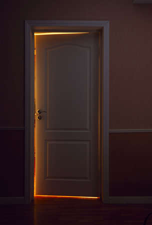 hoteldeur: open door to illuminated room from dark hall Stockfoto