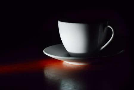 white cup on saucer in dark photo