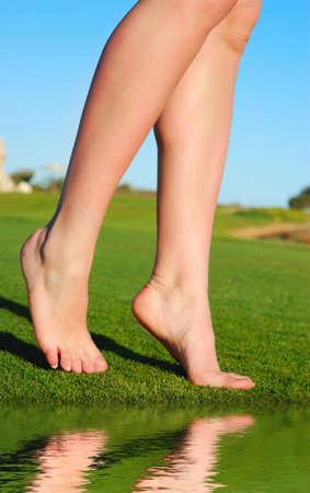 weightless: beautiful female legs on grass near lake Stock Photo