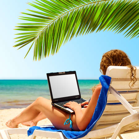 internet surfing: woman surfing internet on the beach.  Stock Photo