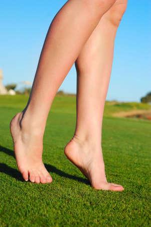 weightless: hermosas piernas femeninas sobre c�sped Foto de archivo