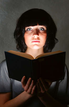 young beautiful woman is illuminated by a glowing book photo