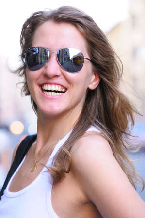 young smiling woman on bright city street photo