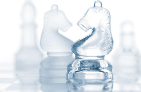 transparent glass chess pieces isolated on white  photo